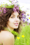 Girl wearing a wreath of wild flowers in the field Stock Photo