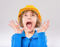 Girl wearing yellow hard hat. Emotional portrait of attractive caucasian girl wearing safety yellow hard hat. Surprised or shocked child looking up, isolated on Royalty Free Stock Photo