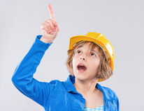 Girl wearing yellow hard hat. Emotional portrait of caucasian little girl wearing safety yellow hard hat. Shocked or surprised child pointing up and looking away Royalty Free Stock Photography