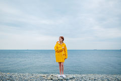 Girl wearing yellow raincoat. Portrait of young woman wearing bright yellow raincoat on background of ocean Stock Image