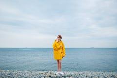 Girl wearing yellow raincoat Stock Image