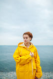 Girl wearing yellow raincoat. Portrait of young woman wearing bright yellow raincoat on background of ocean Stock Photography