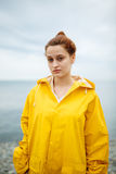 Girl wearing yellow raincoat. Portrait of young woman wearing bright yellow raincoat and looking at camera on background of ocean Stock Photos