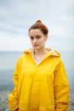 Girl wearing yellow raincoat Stock Photos