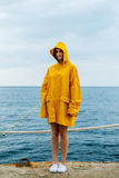 Girl wearing yellow raincoat. Portrait of young woman wearing bright yellow raincoat and looking at camera on background of ocean Stock Images