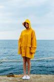 Girl wearing yellow raincoat Stock Images