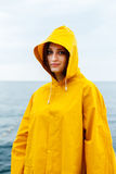 Girl wearing yellow raincoat. Portrait of young woman wearing bright yellow raincoat and looking at camera on background of ocean Royalty Free Stock Image