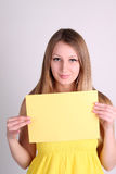Girl wearing yelow clothing and showing blank card Royalty Free Stock Image