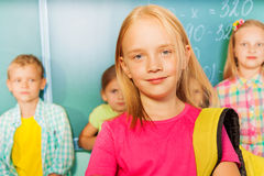 Girl wears bag near blackboard, pupils behind her Royalty Free Stock Image