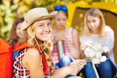 Girl wears hat holds sticks with marshmallow Stock Images