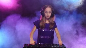 Girl wears headphones and starts plays on turntable. Slow motion. Girl wears headphones and starts plays on turntable, headphones on head, dancing to music stock video