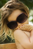 Girl wears a large adult sunglasses Royalty Free Stock Photo