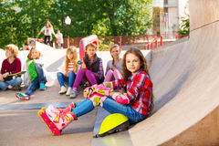 Girl wears in-line skates sits in front with mates Stock Photos