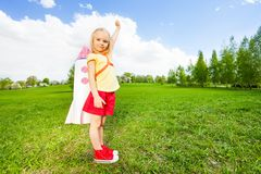 Girl wears rocket toy on shoulders holding arm up Stock Photos