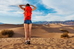 Girl wears rucksack, stands with Death valley view Royalty Free Stock Images