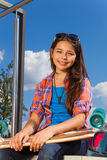 Girl wears sunglasses and sits with skateboard Royalty Free Stock Images