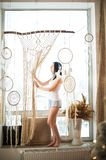 The girl weaves macrame, catchers. Young woman hobby weaving. Dream catchers, macrame on the window. The girl weaves macrame, dream catchers. Young woman hobby royalty free stock images