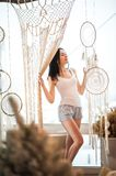 The girl weaves macrame, catchers. Young woman hobby weaving. Dream catchers, macrame on the window. The girl weaves macrame, dream catchers. Young woman hobby royalty free stock image