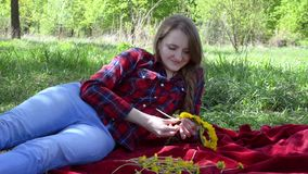 A girl weaves a wreath of dandelions sitting on a plaid in the park. Spring.  stock video