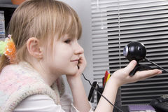 Girl and web camera. Little girl look to the web camera in her hand and smile Stock Photos