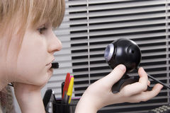 Girl and web camera. Little girl look to the web camera in her hand and smile Stock Photography