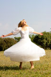 Girl in a wedding-dress. Twirled on a lawn Royalty Free Stock Photo