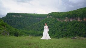 A girl in a wedding dress and black boots dances on the lawn in the mountains.