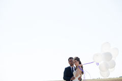 Girl in wedding dress and husbad with ballons in hands Royalty Free Stock Image