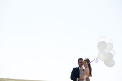 Girl in wedding dress and husbad with ballons in hands Stock Image