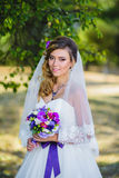 The girl in a wedding dress with purple bow Stock Photography