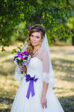 The girl in a wedding dress with purple bow Royalty Free Stock Image