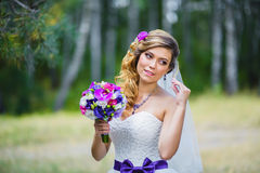 The girl in a wedding dress with purple bow Stock Photos