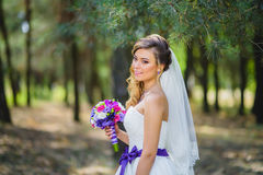 The girl in a wedding dress with purple bow Stock Images