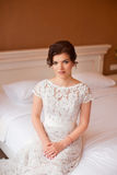 The girl in a wedding dress sits on  sofa Royalty Free Stock Photo