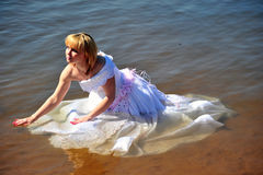 The girl in a wedding dress in water Royalty Free Stock Image