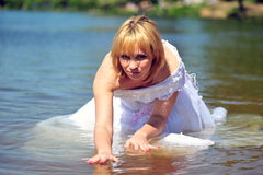 Girl in a wedding dress in water Stock Image