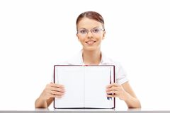 Girl with a weekly journal. Attractive business girl shows the blank turn of a weekly journal, isolated Stock Images
