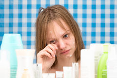 Girl is weeping in bathroom in front of cosmetic products Stock Photography