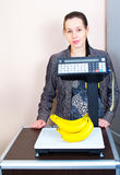 Girl weighing bananas in market Royalty Free Stock Images