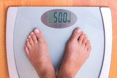 Girl on weighing. Perfect weight for a girl. Libra shows that a stock images