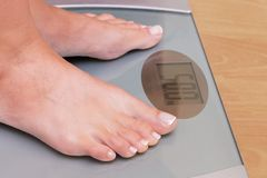 Girl on weighing. Perfect weight for a girl. Libra shows that a royalty free stock image