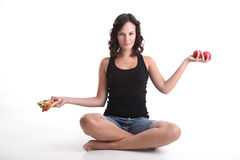 Girl weighing pizza and apples. A sitting young girl weighing pizza and apples Royalty Free Stock Image