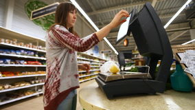 Girl weighs purchase of electronic scales in the supermarket stock footage