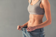 Girl and weight loss. Cropped image of girl pulling her big jeans and showing weight loss Stock Photos