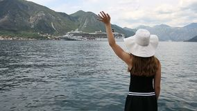 The girl welcomes the cruise ship Kotor bay Montenegro