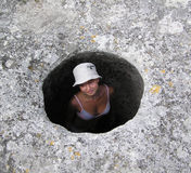 Girl in a well. Girl looking out an ancient well stock images