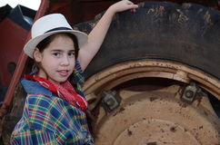 Girl in western clothes with a tractor Stock Images