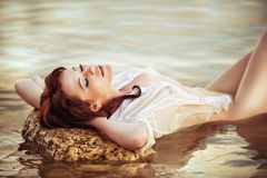 Girl in wet clothes lying in the water. Hot summer Ukrainian girl in tight wet white shirt lying in water on the beach Stock Image
