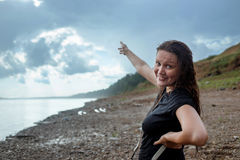 The girl in wet clothes under a heavy rain outdoors. Woman point to rain clouds Royalty Free Stock Photo