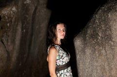 Girl with wet hair stands between stones. Stock Photos